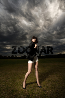 Young caucasian woman in a park with stormy background