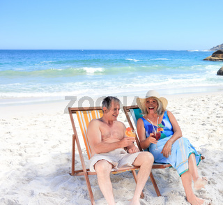 Senior couple sitting on deck chairs