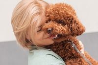 Portrait blonde woman hugging curly Toy poodle