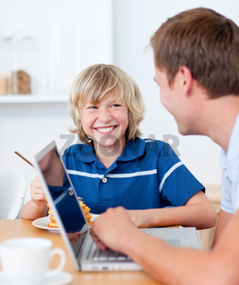 Smiling boy having breakfast while his father using a laptop