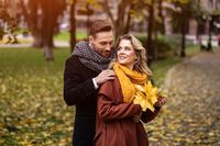 Loving couple in an autumn park. Husband and a wife hugged smile looking at each other in the autumn park. Outdoor shot of a young couple in love having great time in a autumn park
