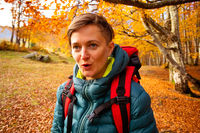 The woman hiker travels in the woods is looking around