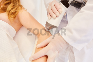 Frau bekommt  Lasertherapie am Oberarm