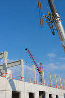 A view on a building construction site with building cranes and blue sky.