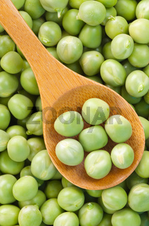 Fresh grren peas on wooden spoon