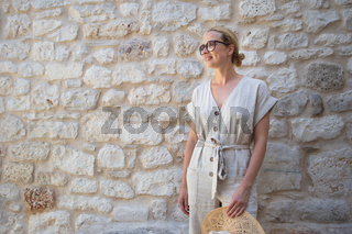 Portrait of beautiful cheerful blonde woman wearing one piece summer dress and summer hat, standing in front of old medieval stone wall. Summer vacation portrait concept.