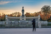 Madrid Spain, sunrise city skyline at El Retiro Park with woman tourist and autumn foliage season