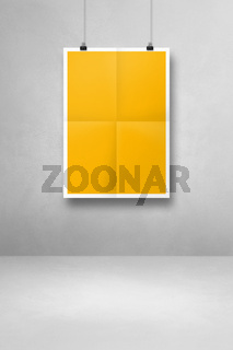 yellow folded poster hanging on a clean wall with clips