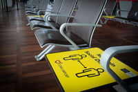 Yellow social distance sign on terminal chairs at airport. Safety measures from covid-19 pandemic