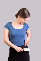 Young woman with lint roller