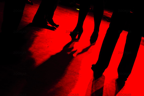 red dance floor with black silhouettes of dancing