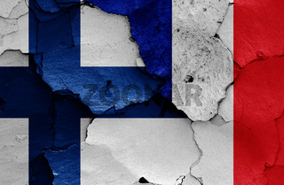 flags of Finland and France painted on cracked wall