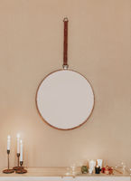 Minimalistic interior design of apartment with round mirror hanging on beige wall, dressing table