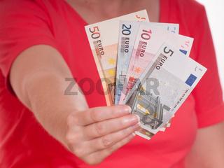 Weibliche Hand hält Euroscheine nach vorne
