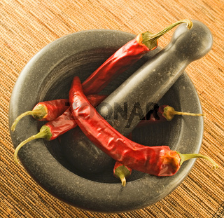 stone mortar with red chillies