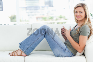 Woman sitting sideways on the couch, cup in hands, smiling and looking forward