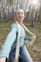 woman in a blue jumper takes a selfie in a birch forest