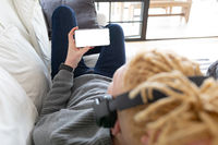 African american man lying on the couch holding the smartphone with copy space