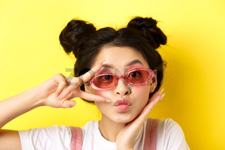 Summer fashion concept. Cute and glamour asian girl in sunglasses, showing v-sign kawaii and looking at camera, standing on yellow background