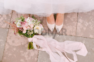 The bride's legs in graceful white shoes peek out from under the skirt, next to the bride's bouquet lies, close-up