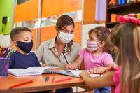 Tagesmutter und Kinder mit Gesichtsmaske in Vorschule