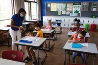 African american female teacher spraying hand sanitizer on hands of boy at elementary school