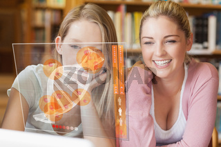 Two smiling students looking at laptop and futuristic interface
