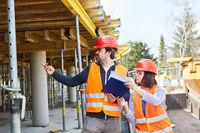 Vorarbeiter und Architektin mit Checkliste auf Baustelle