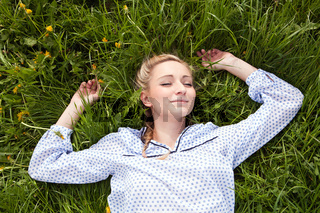 young woman lying in green gras happy