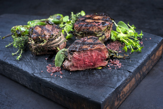 Traditional barbecue dry aged angus medaillon beef filet steak natural with herbs and red wine salt served as close-up on a charred wooden board