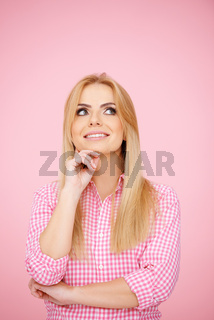 Thoughtful blond girl on pink