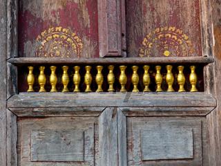 alte verwitterte Holztüre mit goldener Verzierung