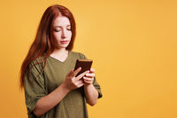 young woman reading text message on smartphone or mobile cell phone