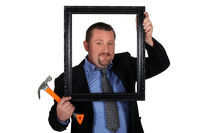 Man in a suit with a picture frame and hammer