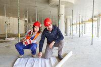 Arbeiter und Architekt mit Grundriss auf einer Baustelle