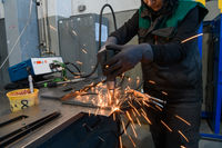 a woman working in the modern metal production and processing industry welding the product and prepares it for a cnc machine