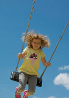 Child swings high. With blue sky in background. Portrait format