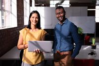 Portrait of smiling diverse male and female colleague standing in office looking at laptop together