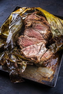 Slow cooked Omani lamb shuwa coated in rub of spices and wrapped in banana leaves sliced and served as close-up on a rustic metal tray