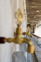 Closeup of a golden water on a wall with other water taps on the background