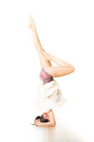 Portrait of active sporty young woman practicing standing on head yoga pose in yoga studio. Healthy active lifestyle