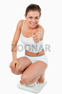 Portrait of a woman squatting on scales with the thumb up