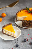 Cheese cake with mango fruit on a grey background. Cheese cake with passion fruit sauce on top decorated with berries and fruits