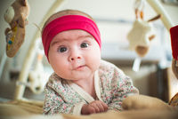 Portrait of adorable baby with funny expression on the floor indoors