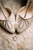 Women's earrings in the shape of leaves on the toes of the bride's white shoes with an engagement ring on a rough texture.