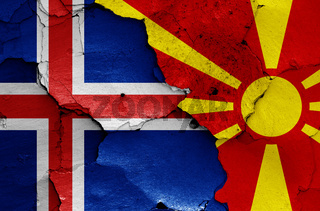 flags of Iceland and North Macedonia painted on cracked wall