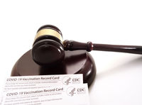 Legal gavel and US CDC COVID-19 Vaccination Record card