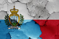 flags of San Marino and Poland painted on cracked wall