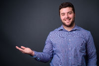 Portrait of happy young handsome overweight bearded businessman