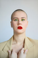 Vertical portrait of beautiful bald woman with creative make-up. Isolated.